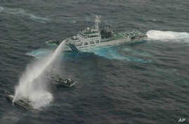 In this photo released by Japan Coast Guard 11th Regional Headquarters, a Japan Coast Guard patrol boat uses water cannon to warn a Taiwan's leisure boat, left, and Taiwan Coast Guard boat off Uotsuri in Japanese and Diaoyu Dao in Chinese,January 24,