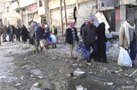 Civilians carry their belongings as they walk towards a meeting point to be evacuated from a besieged area of Homs, Syria, Feb. 7, 2014.