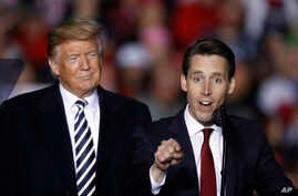 President Donald Trump listens as Republican Senate candidate Josh Hawley speaks during a campaign rally at Columbia Regional Airport, Nov. 1, 2018, in Columbia, Mo.