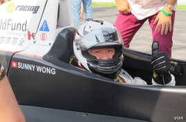 Sunny Wong in the PS Racing car with Child Fund decals in Zhuhai, China, Sept. 15, 2013. (Photo: Marianne Brown for VOA)