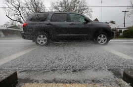 A car sends hail stones flying as it drives through a sudden hail storm that passed through the area Feb. 26, 2018, in Sacramento, Calif.