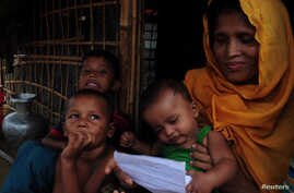Sait Banu sits at her bamboo shelter with her children at a Rohingya refugee camp in Cox's Bazar, Bangladesh, holding a letter she received from her husband imprisoned in Myanmar, June 28, 2018.