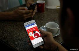 A cellphone user looks at a Facebook page at a shop in Latha street, Yangon, Myanmar August 8, 2018