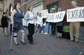 Boston Marathon bombing victim Erika Brannock, foreground left, and her mother Carol Downing, foreground right, walk past demonstrators outside federal court in Boston, June 24, 2015.