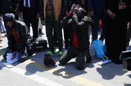 Somali migrants kneel and pray after arriving back in the Somali capital, Mogadishu, Feb. 17,  2018. (Somali Ministry of Information)