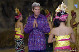 U.S. Secretary of State John Kerry gestures as he arrives for the Asia-Pacific Economic Cooperation [APEC] Summit official dinner in Nusa Dua on the Indonesian resort island of Bali, Oct. 7, 2013.