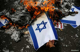 A protester burns an Israeli flag during a rally to condemn Washington's decision to recognize Jerusalem as Israel's capital, outside the U.S. embassy in Jakarta, Indonesia, Dec. 15, 2017.