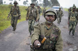 Congolese army soldiers march into Kibumba town after recapturing it from M23 rebels over the weekend, around 25km from the provincial capital Goma, in eastern Congo Monday, Oct. 28, 2013.