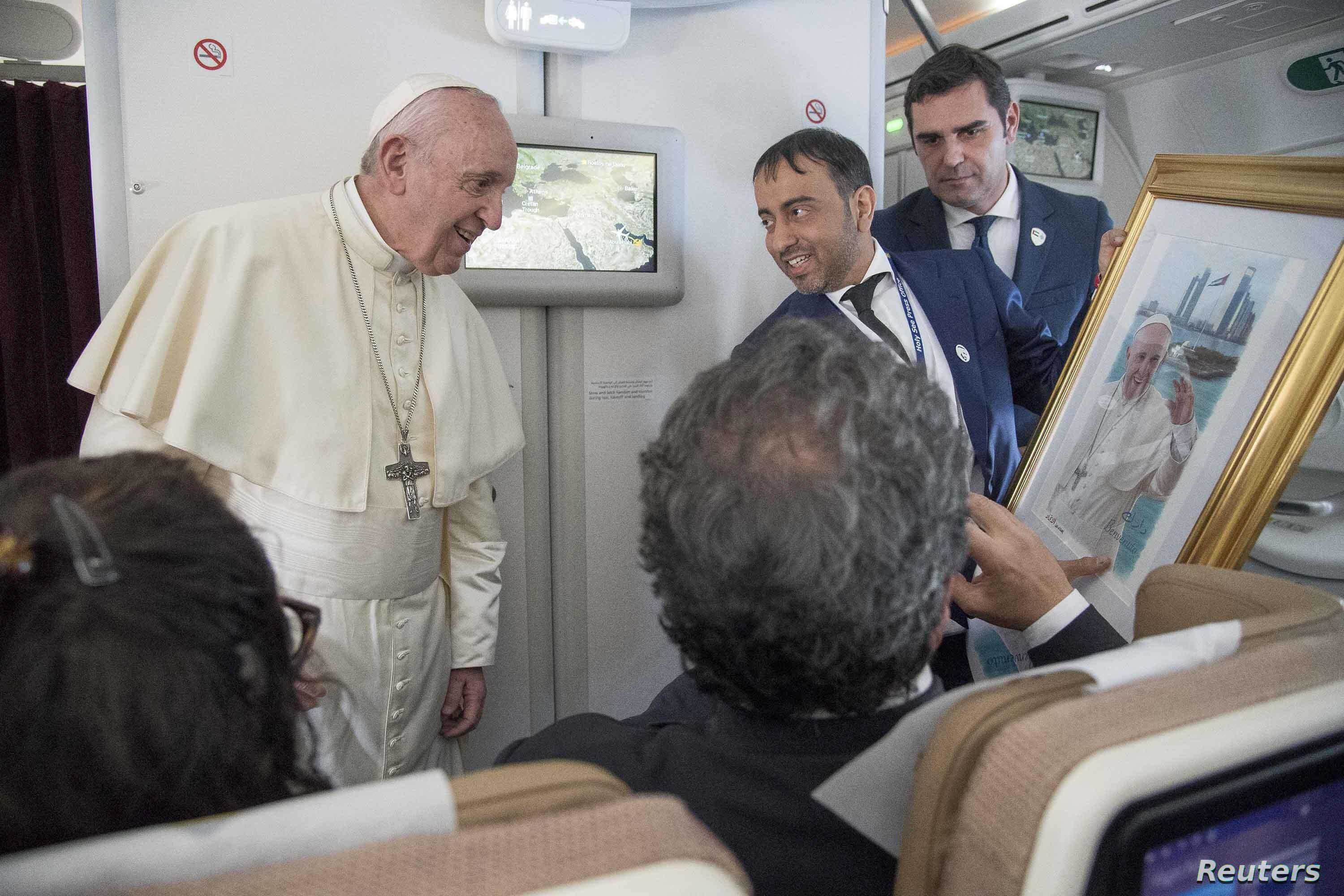 Pope Francis receives a gift from a journalist during a questions session after his visit to Abu Dhabi, United Arab Emirates, Feb. 5, 2019.