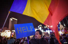 A man holds a cardboard in the colors of the European Union reading 'HELP' as he protests in front of the Romanian Government headquarters in Bucharest, Dec. 10, 2017.