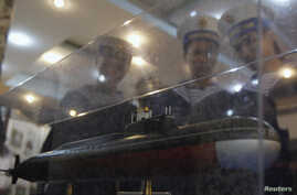 FILE - Sailors look at a model of a submarine at an exhibition as part of the 50th anniversary celebrations of the establishment of the 125 Naval Transport Brigade, also known as the No Number Naval Shipsm, in Vietnam's northern port city of Hai Phon
