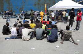 Migrants sit after disembarking from a merchant ship at the Sicilian harbour of Catania, southern Italy, May 5, 2015. Around forty migrants died in the Mediterranean on Sunday, according to survivors of the journey who arrived on the southern Italian