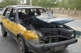 A car damaged by a bomb blast is seen in front of police headquarters in Nigeria's northeastern city of Maiduguri June 8, 2012.