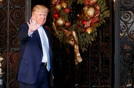 President-elect Donald Trump stands at the entrance of Mar-a-Lago and waves to reporters after meeting with Carlyle Group co-founder and co-CEO David Rubenstein, Wednesday, Dec. 28, 2016, in Palm Beach, Florida.