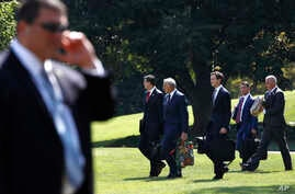 FILE - Members of President Donald Trump's administration walk past a Secret Service agent as they follow Trump to the Marine One helicopter on the South Lawn of the White House in Washington, Aug. 4, 2017.