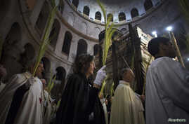 Christian clergy and worshipers holds palm fronds during a procession in the Church of the Holy Sepulcher in Jerusalem's Old City March 24, 2013.