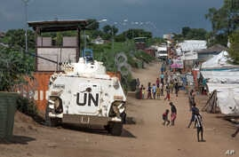 In this photo taken Monday, July 25, 2016, some of the more than 30,000 Nuer civilians sheltering in a United Nations base in South Sudan's capital Juba for fear of targeted killings by government forces walk by an armored vehicle and a watchtower ma
