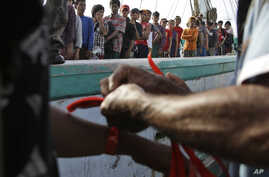 Government official puts wrist bands on recently rescued Burmese fishermen for identification purposes upon their arrival in Tual, Indonesia, April 4, 2015.
