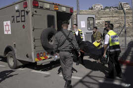 Israeli emergency services personnel carry the body of a Palestinian, identified as Naim Safi, at a checkpoint near Jerusalem, Feb. 14, 2016.