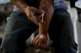 FILE - A man injects heroin, in an area popular with users behind an abandoned home in Humacao, Puerto Rico, Dec. 14, 2018.