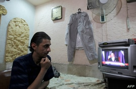 Syrian flower shop owner watches live joint United Nations press conference, Damascus, Sept. 14, 2013.