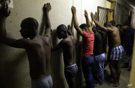 Men stand against a wall as police officers search their room during a raid at an Alexandra township hostel considered a hot spot for anti-immigrant attacks in Johannesburg, South Africa, April 23, 2015.