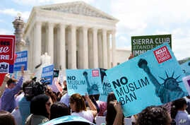 Protesters hold up signs and call out against the Supreme Court ruling upholding President Donald Trump's travel ban outside the the Supreme Court in Washington, June 26, 2018.