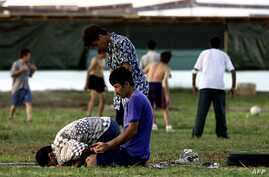 FILE - A small group of Muslim refugees pray at sunset while others play soccer at an Australian-run camp for asylum seekers on the small Pacfic island of Nauru, Sept. 20, 2001. Australia run similar camps on Manus Island in Papua New Guinea.