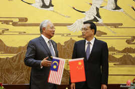 Malaysia's Prime Minister Najib Razak (L) speaks to China's Premier Li Keqiang during a signing ceremony at the Great Hall of the People in Beijing, May 29, 2014.