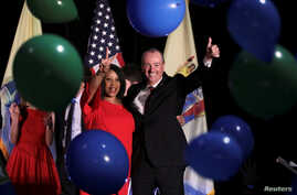 FILE - Phil Murphy, Governor-elect of New Jersey, and Shiela Oliver, Lieutenant Governor-elect, wave to supporters at their election night victory rally in Asbury Park, New Jersey, Nov. 7, 2017.