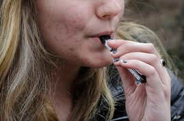 FILE - In this April 11, 2018, photo, an unidentified 15-year-old high school student uses a vaping device near the school's campus in Cambridge, Mass. Health and education officials across the country are raising alarms over wide underage use of e-c