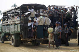 Volunteers and police board vehicles before proceeding to Rohingya refugee camps to collect data for the census in Sittwe, March 31, 2014.