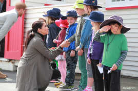 Prince Harry, Duke of Sussex, with Meghan Markle, Duchess of Sussex, meet schoolboy Joe Young, right, and other children outside the Maranui Cafe in Wellington, New Zealand, Oct. 29, 2018.