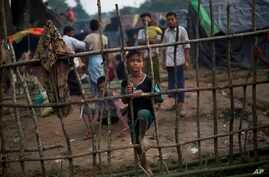A Rohingya child, newly arrived from Myanmar on the Bangladesh side of the border, stands by a wooden fence at Kutupalong refugee camp in Ukhia, Sept. 5, 2017.