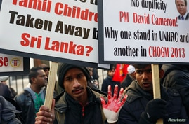 A Tamil demonstrator wears a glove covered with fake blood during a protest near the Commonwealth Secretariat in London, Britain, Nov. 15, 2013.