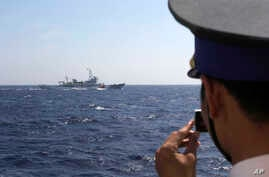 A May 15, 2014 photo shows an officer on board Vietnam Coast Guard 4033 vessel filming China Coast Guard 3411 vessel sailing in waters claimed by both countries in the South China Sea.