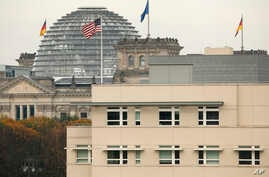 FILE - The American flag flies on top of the U.S. Embassy in front of the Reichstag building that houses the German parliament in Berlin.
