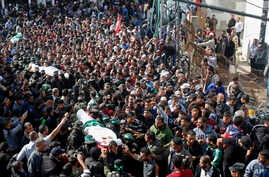 Palestinian mourners carry the bodies of two of the seven Hamas militants who were killed in an Israeli raid late Sunday, during their funerals in Khan Younis, southern Gaza Strip, Nov. 12, 2018.