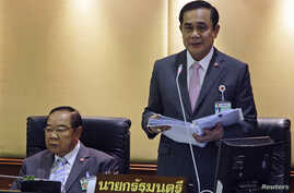 FILE - Thailand's PM Prayuth Chan-ocha (R) reads out his government's policy, as Deputy Prime Minister and Defense Minister Prawit Wongsuwan listens, at the Parliament in Bangkok, Sept. 12, 2014.
