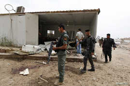 Iraqi policemen inspect the site of a suicide attack at Imam al-Kadhim University in northern Baghdad April 20, 2014.