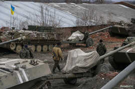 Ukrainian servicemen walk past armoured personnel carriers, military vehicles and cannons at their new position as they pull back from the Horlivka region, near Druzhkivka, eastern Ukraine, Feb. 28, 2015.