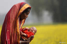 FILE - Monowara holds her 22-day-old grandson Arafat, as she walks through a mustard field on the outskirts of Dhaka.
