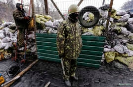 Ukrainian anti-government protesters stand near a passage in a barricade at the site of recent clashes with riot police in Kiev,  Feb. 17, 2014.