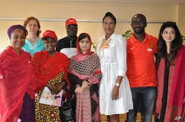 Pakistani activist Malala Yousafzai, who survived being shot by the Taliban because she advocated education for girls, poses for a photograph with the organizers of Bring Back Our Girls campaign, in Abuja, Nigeria, July 13, 2014.