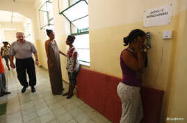 FILE - An Eritrean would-be immigrant talks on the phone at the Lyster barracks detention center for immigrants in Hal Far, outside Valletta, Malta.