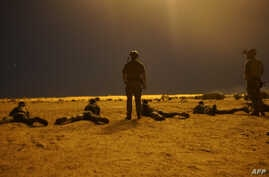 In this photo released by the U.S. Army on March 9, 2017, U.S. Army Special Forces soldiers observe as Nigerien armed forces service members fire their weapons with the assistance of illumination rounds during Exercise Flintlock 2017 in Diffa, Niger....