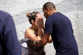 A man comforts a woman at the Raul Brasil State School in Suzano, Brazil, Wednesday, March 13, 2019.