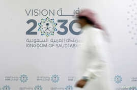 A man walks past the logo of Vision 2030 after a news conference, in Jeddah, Saudi Arabia, June 7, 2016.