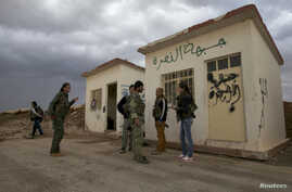 Members of the Kurdish People's Protection Units (YPG) chat together as they stand in front of a base, that used to be for Islamist Syrian rebel group Jabhat al-Nusra, after capturing it from them in Al-Rmelan, Qamshli province, Nov. 11, 2013.