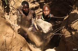 Two artisanal miners digging a pit in a dry riverbed in Karamoja, Uganda. March 2, 2014. (Hilary Heuler for VOA)